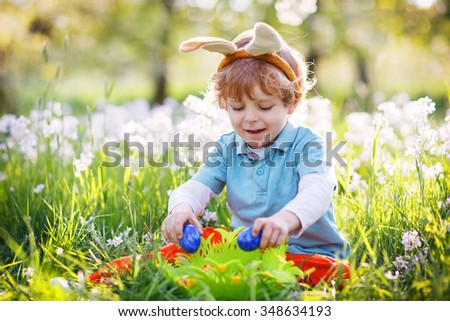 Beautiful little preschool boy having fun with Easter egg hunt and wearing bunny ears - stock photo