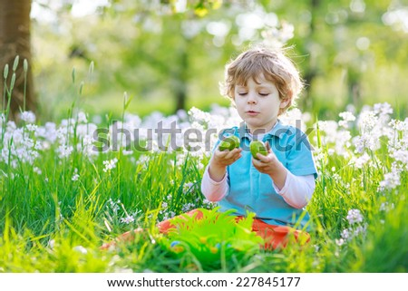 Beautiful little preschool boy having fun with traditional Easter egg hunt on warm sunny day, outdoors. Celebrating Easter holiday. - stock photo