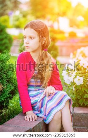 Beautiful little sad girl sitting on bench in summer city park. - stock photo