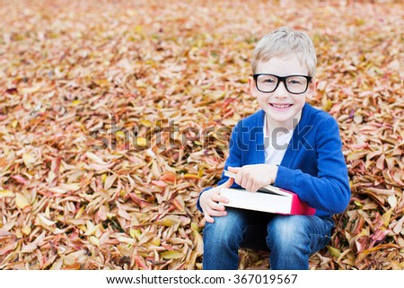 beautiful little schoolboy in glasses reading book ready for new school year in the autumn park - stock photo