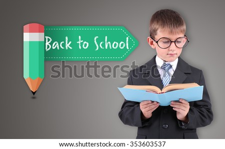 Beautiful little schoolboy with book, on grey background - stock photo