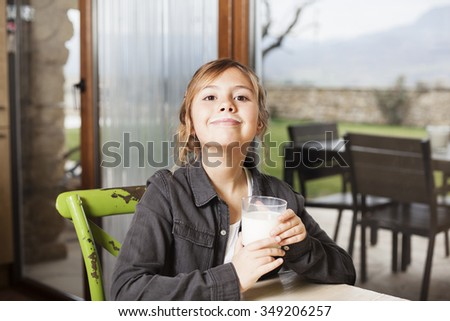 Beautiful little smiling girl holding a glass of milk and showing thump up - stock photo