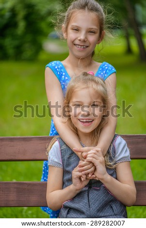 Beautiful little smiling girls sitting on bench in summer city park. - stock photo