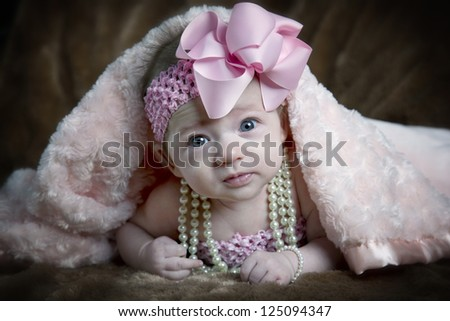 Beautiful little three month old baby girl with pearls and bow peeping from under a blanket - stock photo