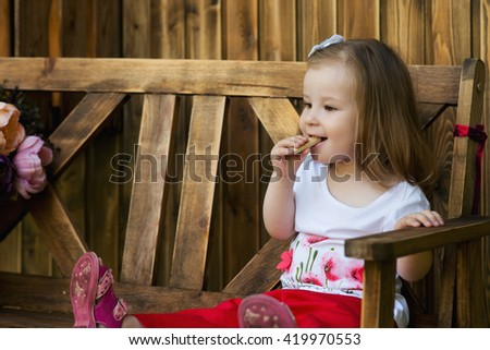 Beautiful little toddler girl sitting on a wooden bench and have a cookie. Kid end healthy food. Fine dinning. - stock photo