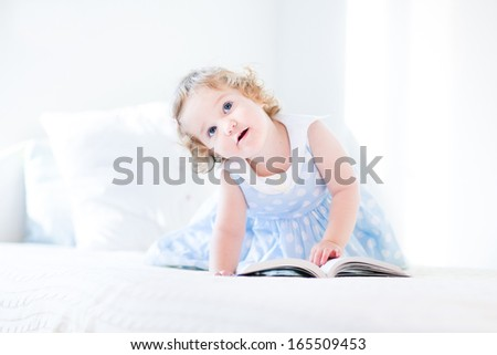 Beautiful little toddler girl with curly hair in a blue dress reading a book on a white bed - stock photo