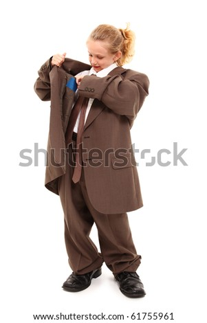 Beautiful little 7 year old girl in baggy suit looking for money in pocket over white background. - stock photo
