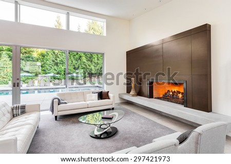 Beautiful living room in luxury home with fireplace, tv, couches, and glimpse of backyard patio - stock photo