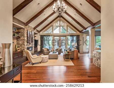 Beautiful living room in luxury home with hardwood floors, tv, fireplace, and vaulted ceiling - stock photo