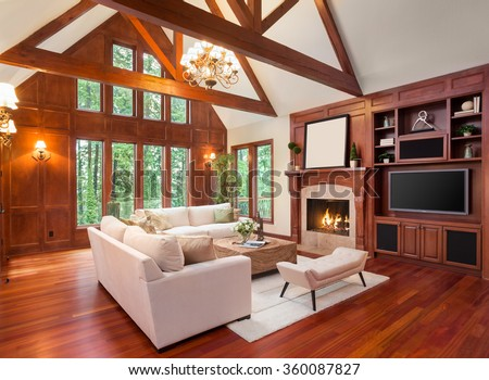 Beautiful living room interior with hardwood floors and fireplace in new luxury home. Includes built-ins with television and vaulted ceilings. Lush green trees fill the exterior view. - stock photo