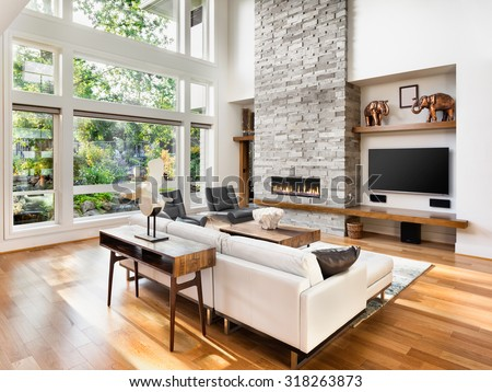 Beautiful living room interior with hardwood floors and roaring fire in fireplace in new luxury home.  - stock photo