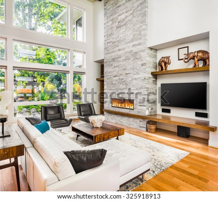 Beautiful living room interior with hardwood floors and roaring fire in fireplace in new luxury home - stock photo