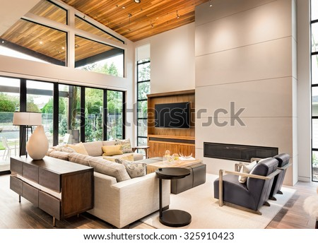 Beautiful living room interior with hardwood floors, vaulted ceiling, and fireplace in new luxury home - stock photo