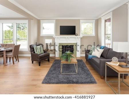 Beautiful living room interior with open floor plan: shows hardwood floors and fireplace in new home, with view of dining room table - stock photo