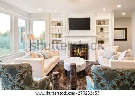 Beautiful living room with hardwood floors and fireplace in new luxury home - stock photo