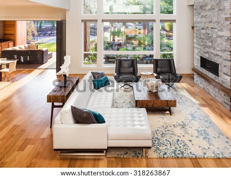 Beautiful living room with hardwood floors and fireplace in new luxury home. View of outdoor patio - stock photo