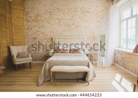 Beautiful loft bedroom with bed near brick wall  - stock photo