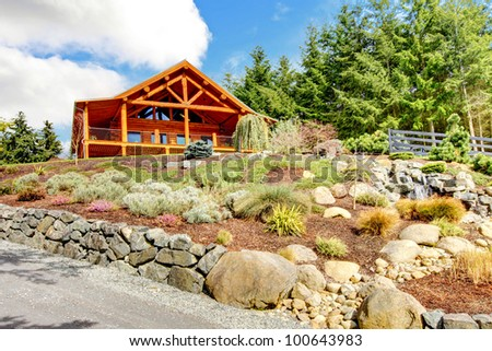 Beautiful Log cabin on the hill with waterfall and flowers. - stock photo