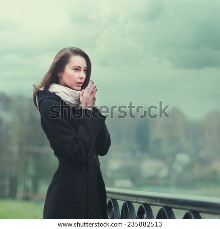 beautiful lonely girl on the waterfront in the city - stock photo