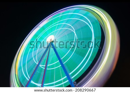 Beautiful Long exposure picture of a ferris wheel rotating, vivid colors. - stock photo