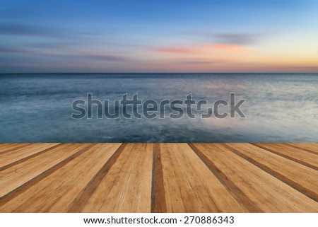 Beautiful long exposure seascape image of calm ocean at sunset with wooden planks floor - stock photo