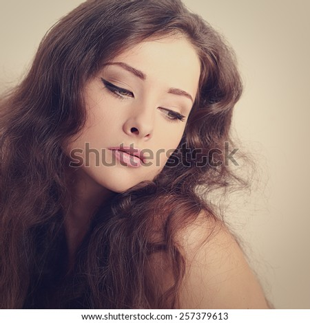 Beautiful long hair brunette woman looking mystery. Color art portrait. Closeup - stock photo
