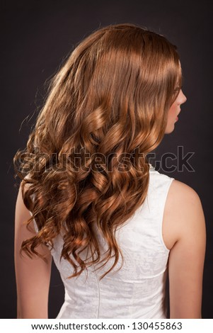 Beautiful long hair Brunette woman with healthy curly dark Hair and stylish hairstyle. Teenager girl beauty model. fashion lady with long curly glossy hairs at studio. Health and beauty products - stock photo