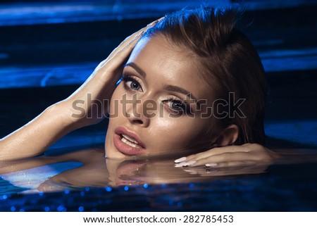 Beautiful long hair female model posing on swimming pool  - stock photo
