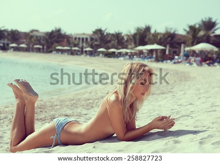 Beautiful long hair female model wearing bikini, posing on the beach, outdoor portrait - stock photo