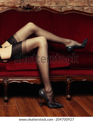 Beautiful long legs of a nude woman in erotic black stockings - stock photo