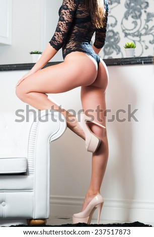 Beautiful long sexy fit female with long legs and perfect butt in lingerie on high heels posing by sofa indoors. Closeup - stock photo