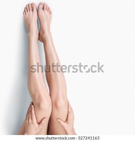 Beautiful long slim female legs isolated on white background - stock photo