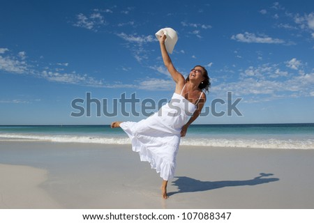 Beautiful looking mature woman in white summer dress joyful at beach holiday, isolated with ocean and blue sky as background and copy space. - stock photo