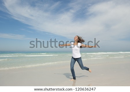 Beautiful looking young woman running cheerful with arms up at beach, isolated with ocean and sky as background and copy space. - stock photo