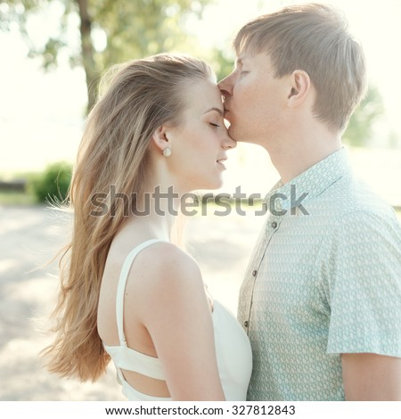 beautiful love romantic couple kissing in the park on a sunny day - stock photo
