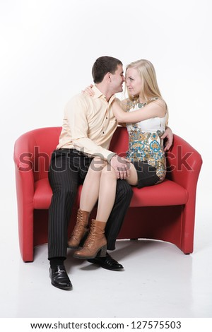 Beautiful loving couple hugging and having fun on red sofa. Happy Couple in Love - stock photo