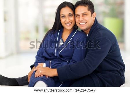 beautiful loving indian couple sitting in bedroom - stock photo