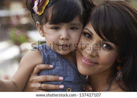 Beautiful loving mother and daughter playing together on sunny day. - stock photo