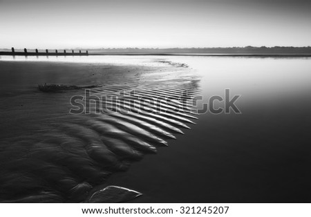 Beautiful low point of view along beach at low tide out to sea with vibrant sunrise sky in black and white - stock photo