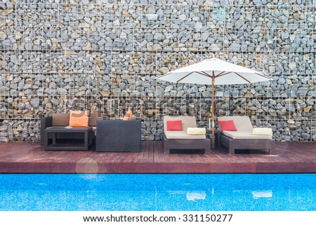 Beautiful luxury chair with umbrella deck and pool resort - stock photo