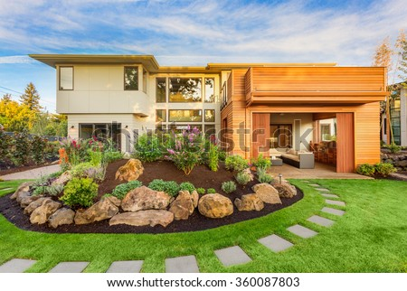 Beautiful Luxury Home Exterior  with Balcony and Green Grass on Sunny Afternoon - stock photo