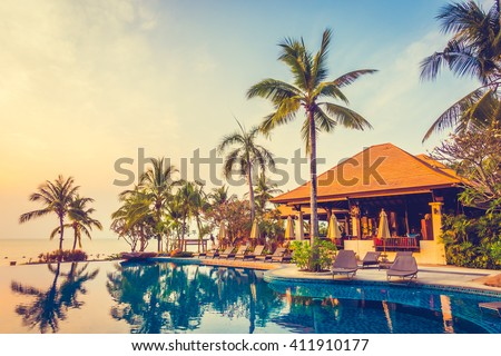 Beautiful luxury Swimming pool with palm tree and sea background in hotel pool resort - Vintage Filter and Boost up color Processing - stock photo