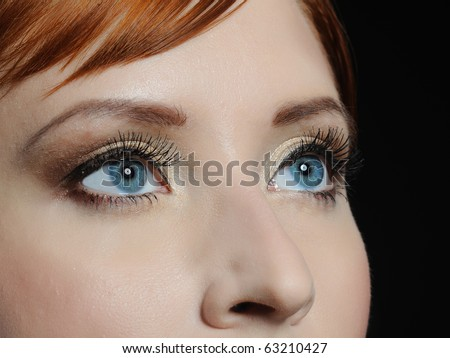 Beautiful macro shot of blue eyes with long lashes and make-up in brown tones - stock photo