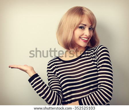 Beautiful makeup blond woman holding and presenting something in the hand. Toned portrait - stock photo