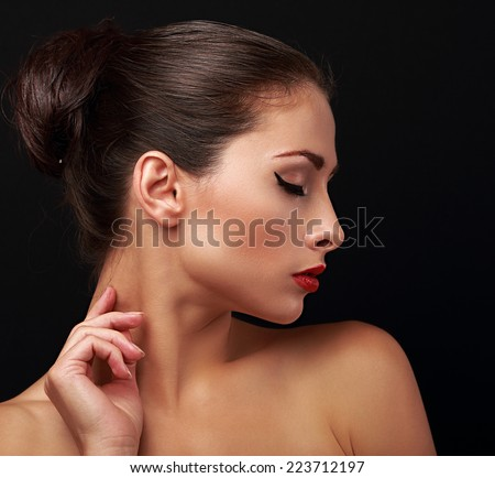 Beautiful makeup woman profile with elegant hairstyle. Closeup portrait on black - stock photo
