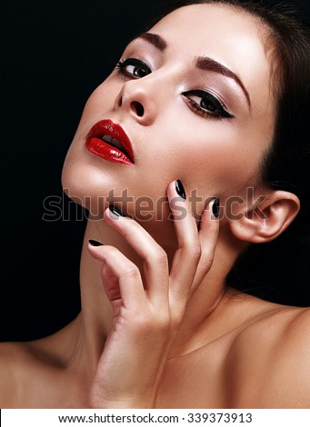 Beautiful makeup woman with bright red lips and black manicured nails on black background. Closeup portrait - stock photo