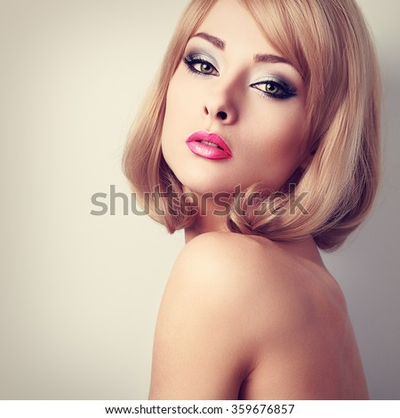 Beautiful makeup woman with green eyes and pink lipstick. Short hairstyle. Closeup toned portrait - stock photo