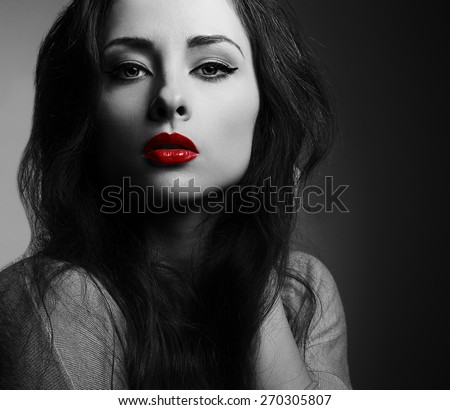 Beautiful makeup woman with red lips looking sexy. Black and white closeup portrait in darkness - stock photo
