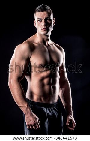 beautiful male athlete shirtless isolated over black background - stock photo