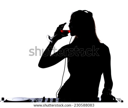 Beautiful male DJ with her headphones is standing at her deck mixing sound and drinking wine. - stock photo
